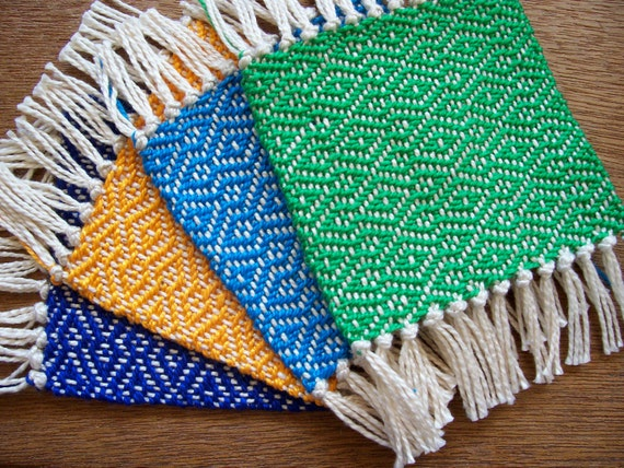 handwoven coaster set in BBQ blue, bright blue, yellow, and green, set of four