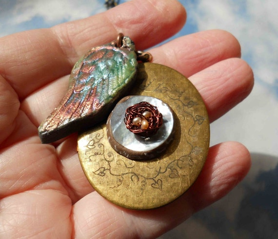Birdnest locket on brass chain w/raku wing