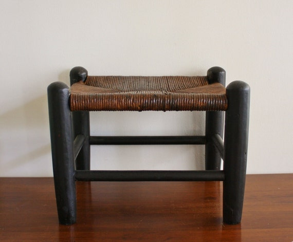 Antique woven footstool with a woven seat