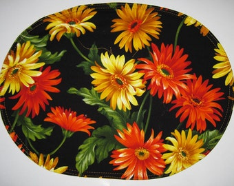 Reversible oval placemats with gerber daisies on black, the reverse is a very bright tone on tone yellow.