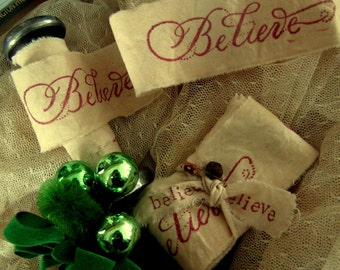 Believe  - Tea dyed hand stamped ribbon trim natural muslin - Comes With Rusty Safety Pin & Bell - 2 YARDS (0305)