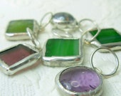 A mix set of 6 stitch markers in purple and green glass