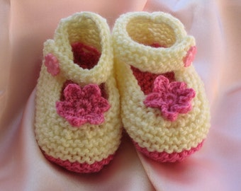 Knitted pink and off-white baby booties with knitted flower