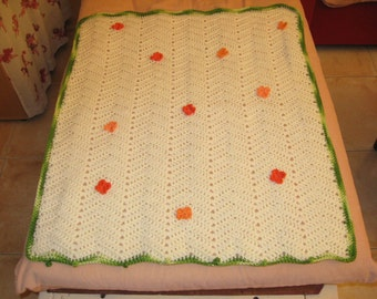 Baby blanket with orange knitted flowers