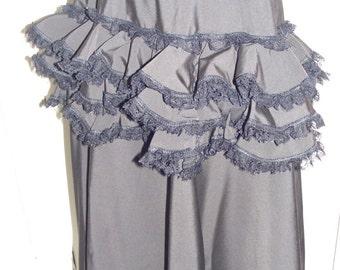 Victorian style black ruffle bustle over skirt.