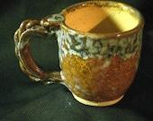 Cream, brown, green and white mug