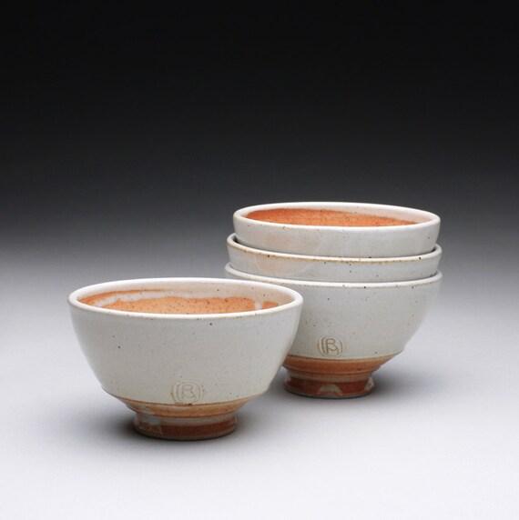 set of four small pottery bowls with white and orange shino glazes