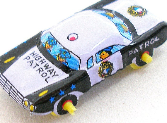 60s tin toy police car, vehicle in black & white.