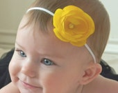 Small yellow ranunculus flower attached to a thin white stretch headband...swarovski crystal center... great for all ages