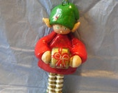 Red, green and gold elf with christmas present