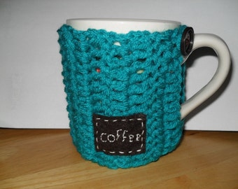 crocheted coffee mug cozy or java jacket in bright peacock blue with eco felt hand stitched coffee tag