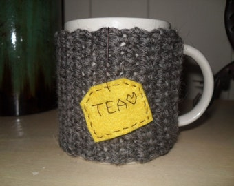 handmade crocheted tea mug cozy in barley brown wool yarn with yellow mustard color hanging tea bag