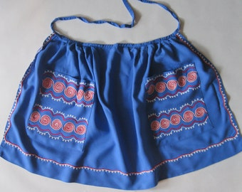 1960's vintage apron in royal blue with red and white swirl embroidery and looped trim