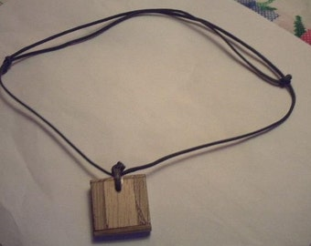 Wooden pendant necklace with adjustable neck cord.