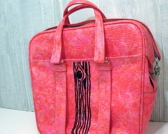 bright pink carry on with black tree