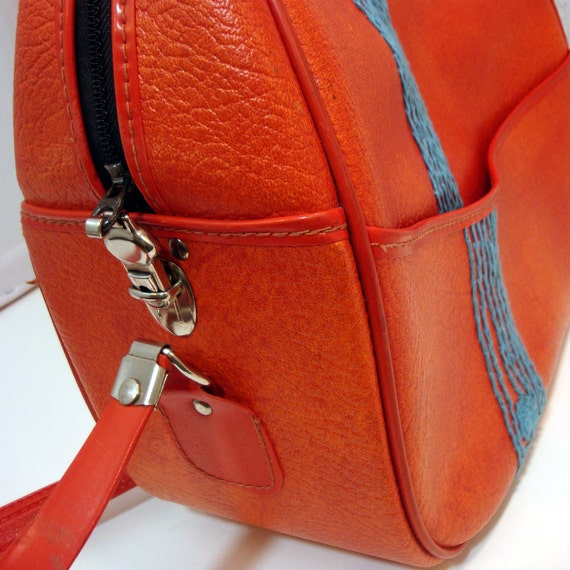 orange carry on with turquoise tree