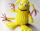 Whimsical monster, crocheted in bright lemon yellow with dusty rose tassels on ears and tail, 5 inches tall