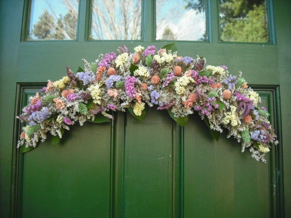 Colorful dried flower arch or swag made with all natural garden flowers in soft pastle colors.
