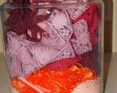 Lot of lace in a variety of types and shades of red, pink and orange.