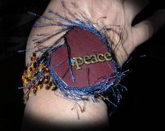 The Word Peace on Leather Heart Stitched to Stretchy gold Sequined Material Bracelet