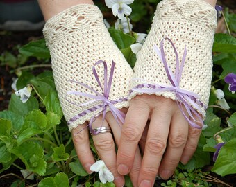 Fingerless crocheted lace gloves with purple color ribbon.