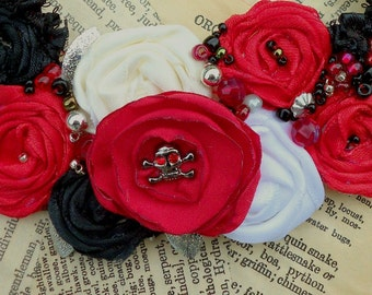 """Tiny Skull with """"Ruby Red"""" Eyes...Black and Red Satin roses, Burnt Organdy, Silver beads and Satin Ribbons"""