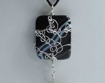 Captured, handmade, unique  large agate tile bead wrapped in sterling silver and suspended on a black suede necklace
