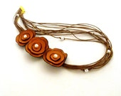 Asymmetric multistrands necklace with leather flowers