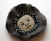 Fabric collage brooch with embroidered face - the shifty eyed one