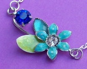 Tiny Blue Flower Charm Necklace with green leaf rhinestones and silver chain