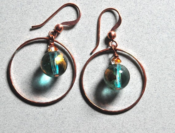 Copper forged hoop earrings with gilded glass center