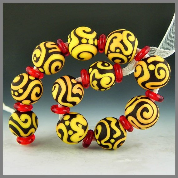 a set of 11 bright apricot graduated etched round handmade lampwork glass beads scrollwork on dark red - Summer Glory