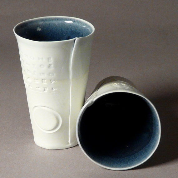 Tumbler -- Four porcelain cups with embossed letters and circles