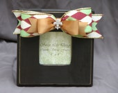 Chocolate brown frame with red, green and cream harlequin ribbon and gold ribbon with rhinestone fleur de lis embellishment