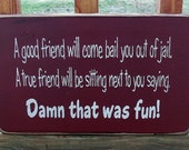 Funny Wood Sign A good friend will come bail you out of jail. A true friend will be sitting next to you saying Damn that was fun