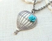 Antique silver hot air balloon necklace with a turquoise mini flower.
