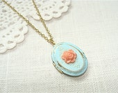 Weathered vintage style locket necklace.  Antique blue with a coral rose and golden chain.  Jewelry by Sweet And Simple.