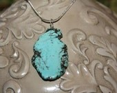 Across the plains of Texas, a flat turquoise nugget on silver plated chain