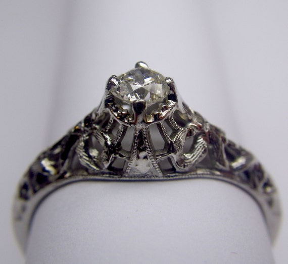 A delicate little diamond antique engagement ring with ribbon-motif filigree design