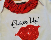 Valentine bodysuit or shirt. Features sequin applique lips and a ruffle collar.