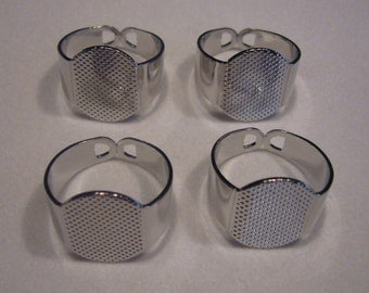 12 platinum tone ring blanks with large glue on pads.