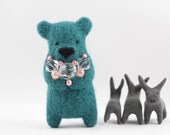 A turquoise blue felted bear brooch