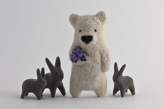 A ivory bear with sparkling crystal flowers in paw brooch
