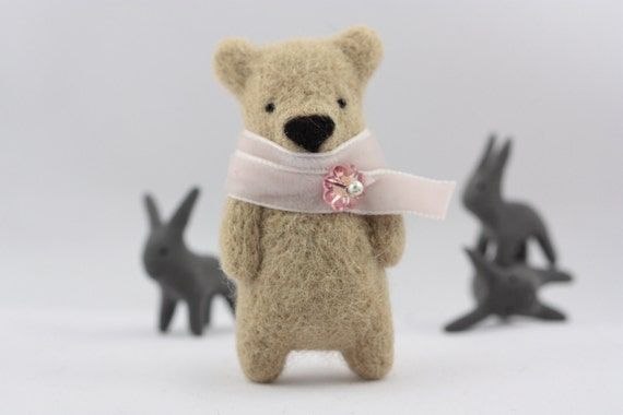 A sandy brown bear with light pink scarf