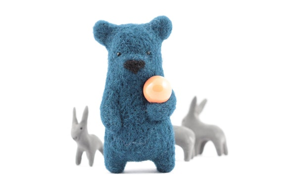 A blue bear holding coral ball brooch