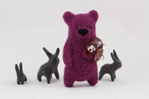 A violet felted bear holding Swarovski crystal flowers in paw brooch