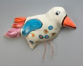 "Handmade Pottery Bird named ""Delbert""- Hand painted underglaze colors red, orange, blue, purple with copper legs. Made to hang on the wall."