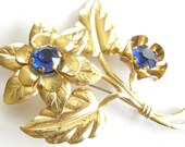 Vintage brass tone floral bouquet brooch with sapphire blue rhinestones