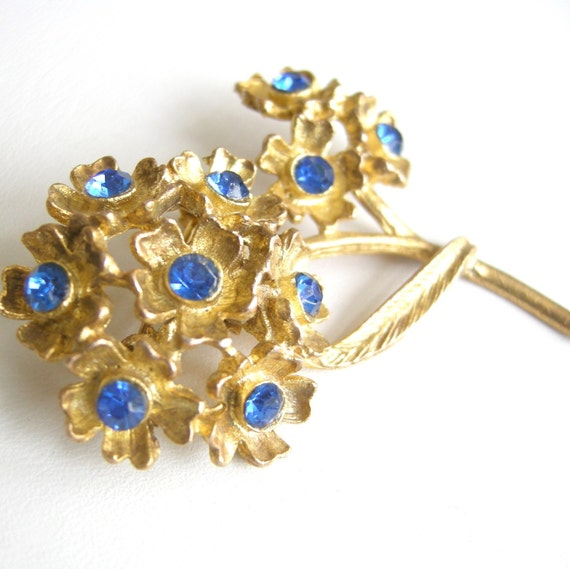 Vintage antiqued brass bouquet brooch with royal blue rhinestones
