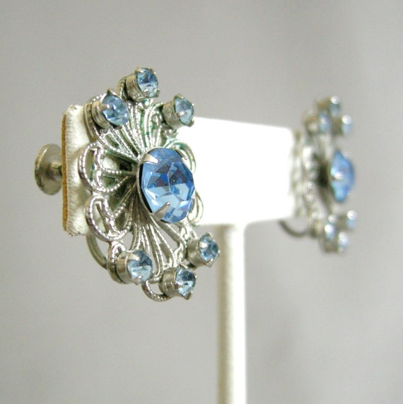 Vintage silver tone filigree earrings with prong-set blue rhinestones